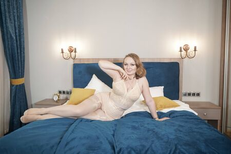 Foto de Voluptuous beautiful young curvy woman wearing retro beige lingerie with vintage stockings with seam. Adult sexy plus size girl in lingerie on the bed. - Imagen libre de derechos