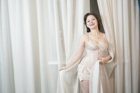 Photo for beautiful pinup girl in old fashionable lingerie and corset stands and holds the curtains, hiding behind them and playing - Royalty Free Image