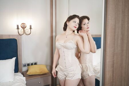 Photo for pretty pin up woman near the mirror standing in fashion lingerie - Royalty Free Image