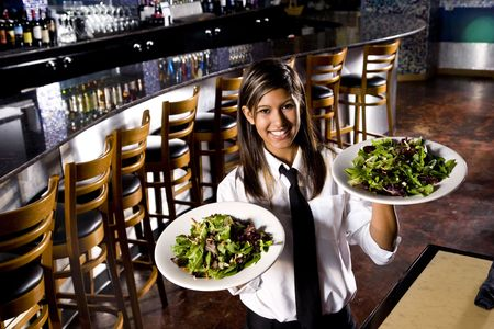 Hispanic waitress in restaurant serving salad plates