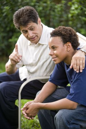 Interracial Hispanic father and African American teenage son together in back yard