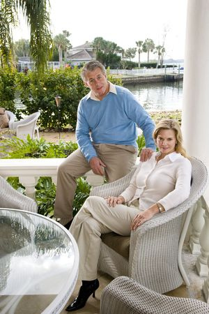 Portrait of mature couple relaxing on waterfront terrace