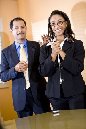 Successful young African-American female office worker getting pat on back from middle-aged Hispanic male manager