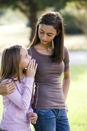 Ten year old girl whispering to her older teenage sister while walking outdoors