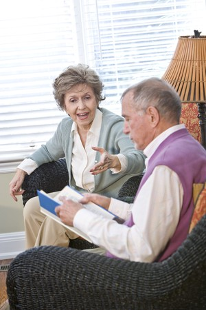 Senior couple chatting in living room reading book, focus on woman talking
