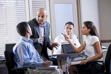 Hispanic business manager meeting with office workers, giving directions