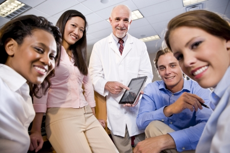 Photo pour Professor wearing lab coat having discussion with college students - image libre de droit