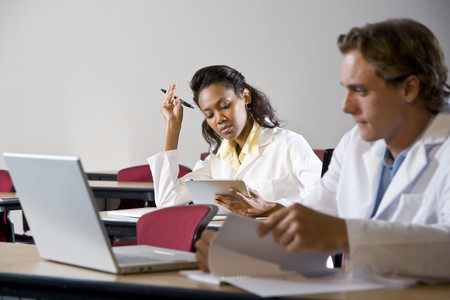 Photo pour Multiracial medical students wearing lab coats studying in classroom - image libre de droit