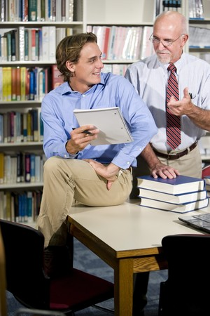 Mature university professor and male student talking in library