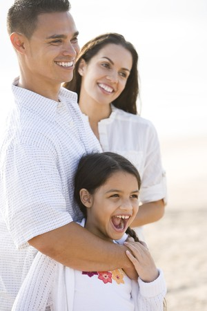 Portrait of happy Hispanic family with young 9 year old daughter laughing
