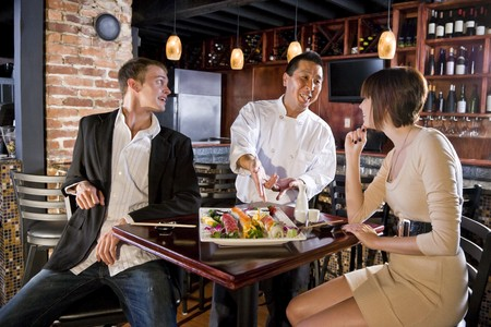 Couple having sushi in Japanese restaurant talking with chef