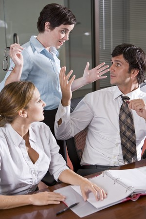 Three office workers in boardroom, having lively discussion