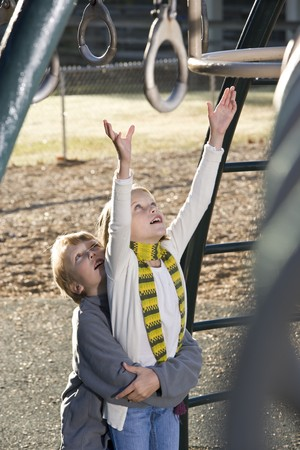 Boy lifting his sister, reaching up for rings on playground