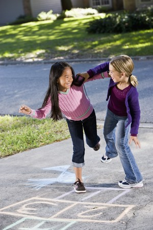 Multiracial friends having fun playing hopscotch on driveway