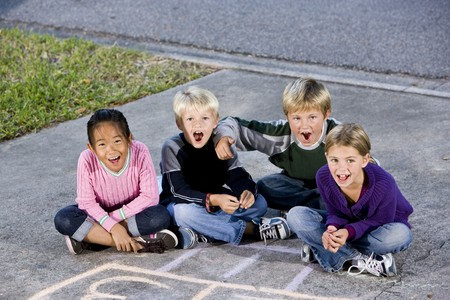Four kids ages 7 to 9 sitting together on drive laughing and shouting