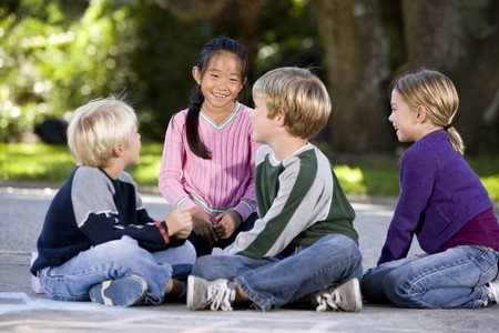 Four multi-ethnic children sitting together smiling outdoors, ages 7 to 9, focus on Asian girl
