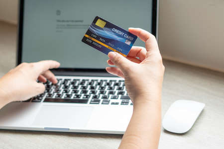 Photo pour Business woman hand hold credit card to shopping internet online bill on computer, Debit saving purchase buy on table background. Shopaholic people retail pay sale money, bank terminal account concept - image libre de droit