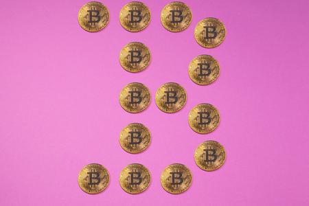 Golden bitcoin coins in form of BITCOIN LOGO or in form of B letter. Bitcoins, golden bitcoins, yellow bitcoins. Cryptocurrency physical golden coins.