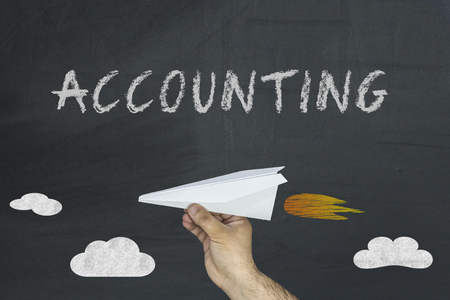 Paper plane and accounting financial concept on blackboard