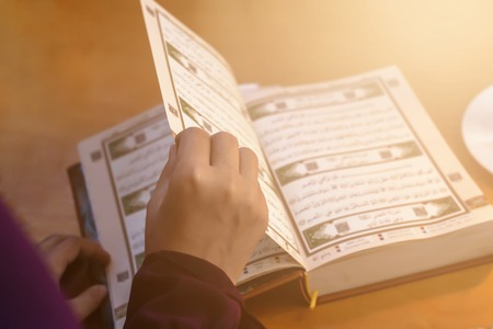 Foto de Praying young muslim woman. Middle eastern girl praying and reading the holy Quran. Muslim woman studying The Quran at home - Imagen libre de derechos