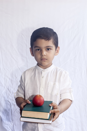 Photo pour Back to school concept. Cute middle eastern boy holding a stack of books against the white background. Portrait of Central Asian kid preparing to go to school. Vetical photo - image libre de droit