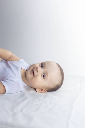 Foto für 6-month baby having fun in white bedding. Cute baby lying on bed. Family, new life, childhood conception. - Lizenzfreies Bild