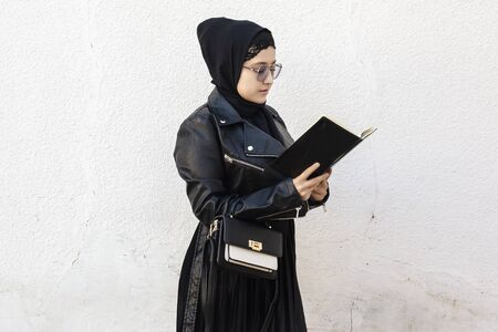 Photo pour Young middle-eastern student girl holding in hands stack of notepads and her handbag. Modern Muslim woman wearing traditional Islamic clothing hijab and leather winter jacket - image libre de droit