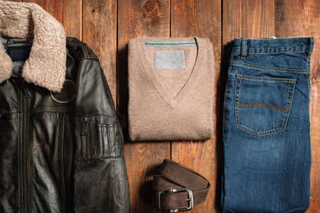 Collection of men's warm autumn clothes on a dark wooden background. Winter jacket, jeans, belt, sweaters. Goods for internet shop.