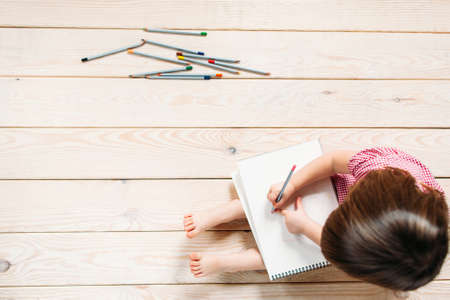 Foto de Unrecognizable child learns to draw with colored pencils. Girl sitting on the wooden floor and draw simple drawings. - Imagen libre de derechos