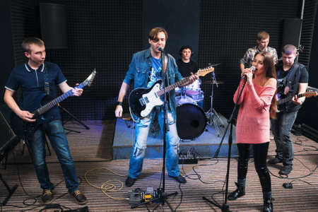Music band alive performance on stage. Two vocalists sing, other member play on their musical instruments. Music group play their song.