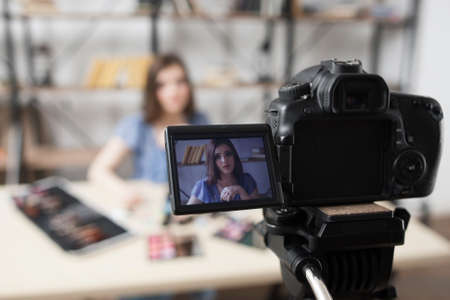 Photo for Young female beauty blogger on camera screen. Beautiful girl recording video at studio. Fashion, makeup, technology concept - Royalty Free Image