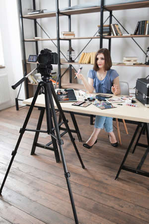 Photo for Young pretty blogger recording video on camera. Modern occupation, woman telling about makeup cosmetics in her vlog - Royalty Free Image