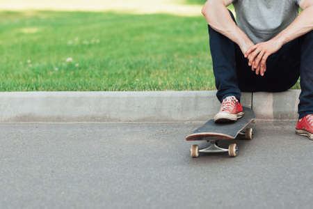 Unrecognizable hipster man sitting with skateboard, extreme sport challenge and competition background with free space. Skateboarder modern urban lifestyle and culture