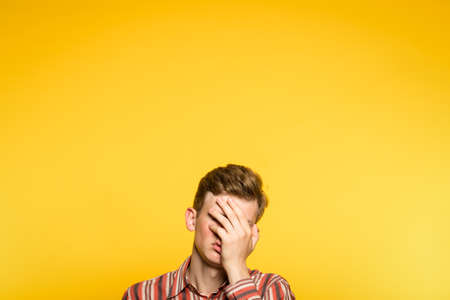 Foto de facepalm. ashamed abashed man covering his face with hand. portrait of a young guy on yellow background popping up or peeking out from the bottom. copy space for advertising. - Imagen libre de derechos