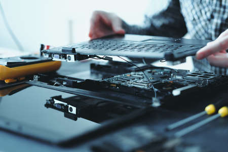 Photo pour electronic renovation in repair shop. engineer disassembling broken laptop removing keyboard - image libre de droit