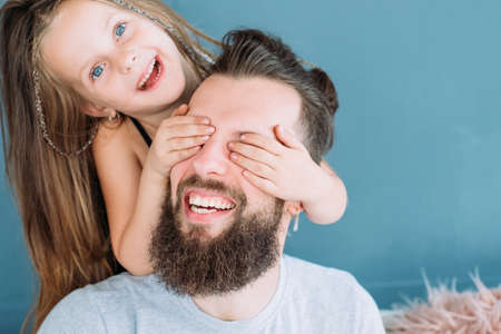 Photo pour playful family leisure. daughters love expression. little girl covering daddys eyes from behind. cute child laughing. joy happiness and fun moments. - image libre de droit