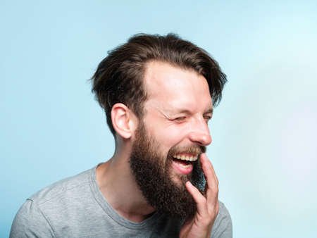 happiness enjoyment and laugh. man with a wide grin. portrait of a young bearded guy on blue background. emotion facial expression. feelings and people reaction.