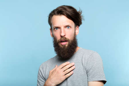 utter indignation. young bearded man shocked from someones impertinence or impudence. people emotional reaction concept. portrait of a casual hipster guy on blue background.