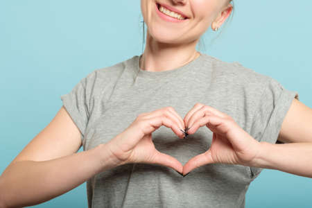 Foto de smiling woman making a heart shape with her hands. love and feelings expression. - Imagen libre de derechos