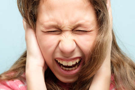 portrait of a screaming girl with tightly shut eyes. child covering ears with hands.