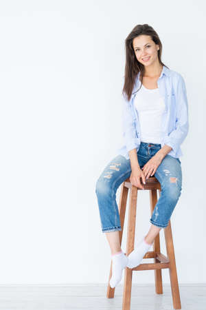 Foto de smiling woman sitting on wooden stool on white background. casual lifestyle. - Imagen libre de derechos