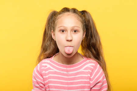 Photo pour girl on yellow background sticking tongue out. cute antics and frolicking concept. - image libre de droit