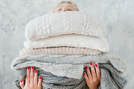 Photo pour woman holding big stack of knitted plaids and blankets. cozy and warm winter home decor - image libre de droit