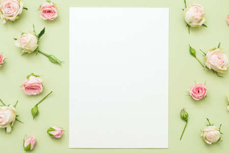 Photo for Womens day greeting card mockup. Blank paper sheet on green background. Rose border decor. - Royalty Free Image