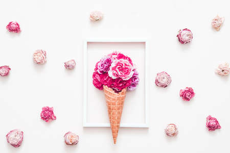 Photo pour Conceptual art. Flower gift composition. Dark pink carnation in cream cone. Photo frame and roses on white background. - image libre de droit