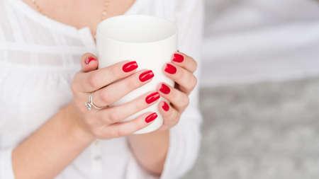Foto de Wake up beverage. Woman manicured hands with white cup of hot morning drink. - Imagen libre de derechos