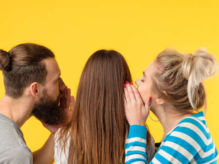 Persuasion concept. Man and woman whispering in girls ear. Copy space on yellow background.