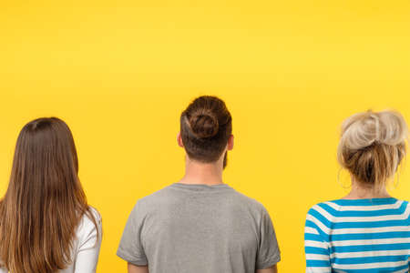 Advertising concept. Three people backview looking at imaginary object. Copy space on yellow background.