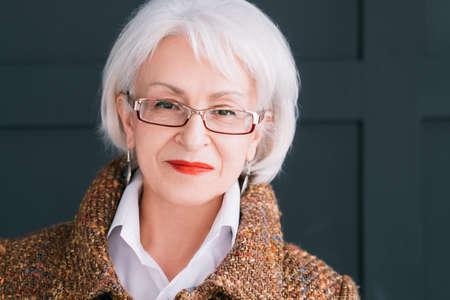 Foto de Senior fashion model portrait. Modern lifestyle. Stylish aged woman in autumn outfit looking at camera. - Imagen libre de derechos