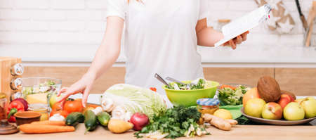 Photo pour Healthy weight loss and nutritional balance. Woman lifestyle. Female with recipe book preparing salad. Organic foods assortment. - image libre de droit